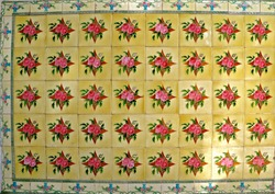 A mosaic of yellow tiles decorated with red flowers. These are typical of the tiles found on the facade of traditional Chinese Peranakan shop houses.