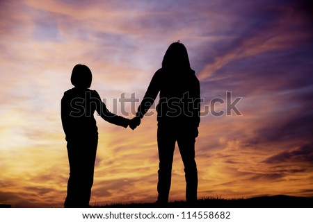 A mother and daughter holding hands watch the sunset.