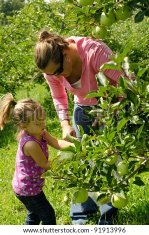 a mother and daughter picking green apples