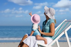 A mother and daughter sitting on a deck chair on a beach and looking up at the sky.