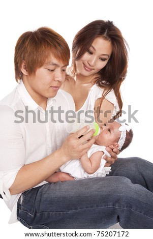 a mother and father feeding their baby girl her bottle.