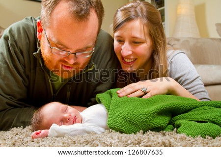 A mother and father with their newborn baby boy while he sleeps on the floor wrapped up in a comfortable green blanket. The parents look happy while gazing at the child.