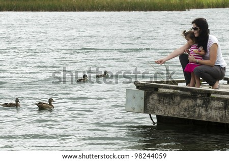 A mother and girl play with ducks on the lake.