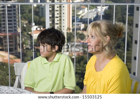 A mother and her child are seated at a table together.  The mother is holding a dog and they are both looking at something straight ahead.  Horizontally framed shot.