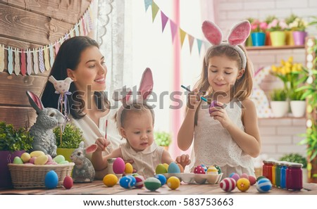 A mother and her daughter are painting eggs. Happy family are preparing for Easter. Cute little child girl wearing bunny ears. #583753663