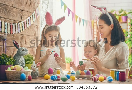 A mother and her daughter are painting eggs. Happy family are preparing for Easter. Cute little child girl wearing bunny ears. #584553592