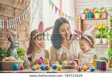 A mother and her daughter are painting eggs. Happy family are preparing for Easter. Cute little child girl wearing bunny ears. #584553628