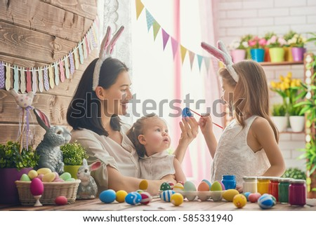 A mother and her daughter are painting eggs. Happy family are preparing for Easter. Cute little child girl wearing bunny ears. #585331940