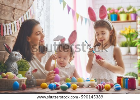 A mother and her daughter are painting eggs. Happy family are preparing for Easter. Cute little child girl wearing bunny ears. #590145389