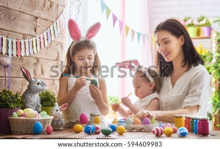 A mother and her daughter are painting eggs. Happy family are preparing for Easter. Cute little child girl wearing bunny ears. #594609983