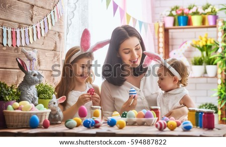 A mother and her daughter are painting eggs. Happy family are preparing for Easter. Cute little child girl wearing bunny ears. #594887822