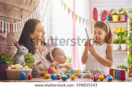 A mother and her daughter are painting eggs. Happy family are preparing for Easter. Cute little child girl wearing bunny ears. #598835543