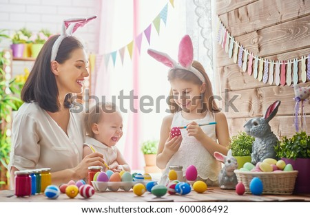 A mother and her daughter are painting eggs. Happy family are preparing for Easter. Cute little child girl wearing bunny ears. #600086492
