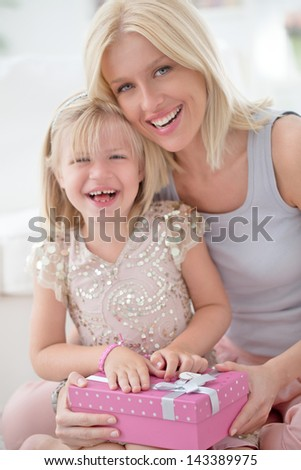 A mother and her daughter sharing happy moments together for the girl's birthday.