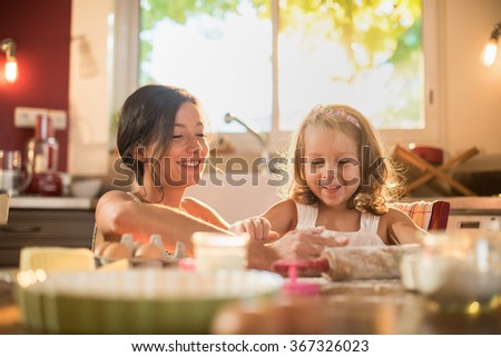 A mother and her four years old blonde daughter are cooking in a luminous kitchen. They are having fun, working on a pasty on a wooden table full of ingredients and a baking pan. Shot with flare