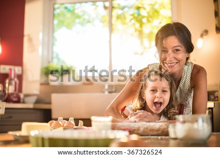 A mother and her four years old blonde daughter are cooking in a luminous kitchen. They are having fun, working on a pastry with a rolling pin on a wooden table full of ingredients and a baking pan.