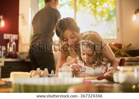A mother and her four years old blonde daughter are cooking in a luminous kitchen. They are making forms on a pasty on a wooden table full of ingredients. The little girl is focused on her actions.