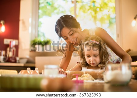 A mother and her four years old blonde daughter are cooking in a luminous kitchen. They are working on a pastry with a rolling pin on a wooden table full of ingredients and a green baking pan.