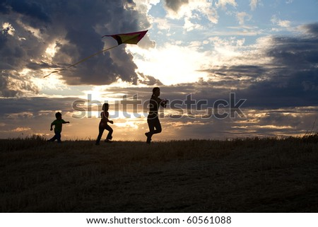 A mother and her two children run with a kite during sunset.