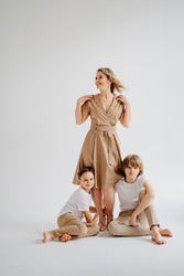 A mother and her two sons in beige and white clothes pose for a photo shoot in the studio. happy single mother. memorabilia for the family. child-parent relationship