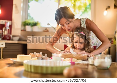A mother and her 4 years old daughter are cooking in a luminous kitchen. They are working on a pastry with a rolling pin on a wooden table full of ingredients and a green baking pan. Shot with flare