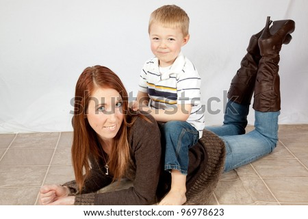 A mother and her young son playing together as he sits on her back as she lays on the floor  and they laugh together