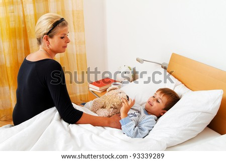 a mother and sick child in bed. influenza. childhood diseases.
