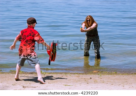 A mother and son duel with water guns at the beach