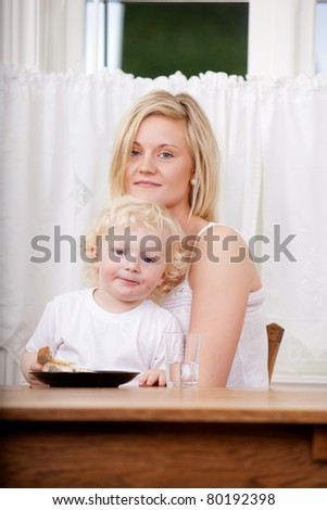 A mother and son looking content at the camera - shallow depth of field critical focus on boy's eyes