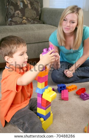 A mother and young son playing with blocks