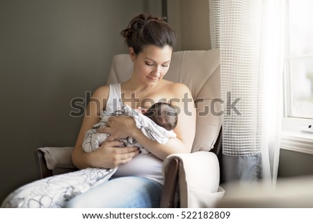 A Mother breastfeeding her little baby boy in her arms.
