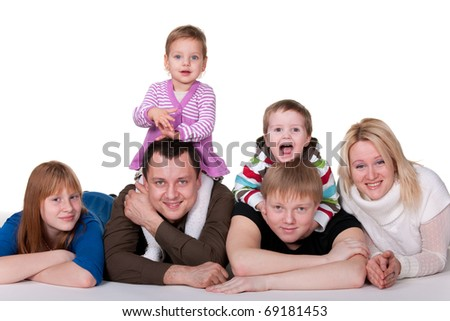 A mother, father, two sons and two daughters are smiling, lying on the studio floor; isolated on the white background