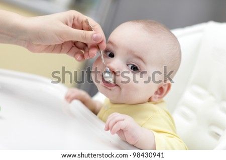 A mother feeding her baby boy with spoon at home - stock photo