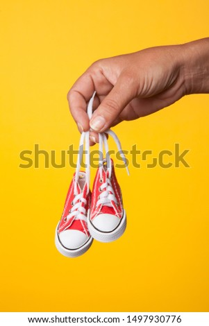 A mother holds on to a pair of baby shoes.