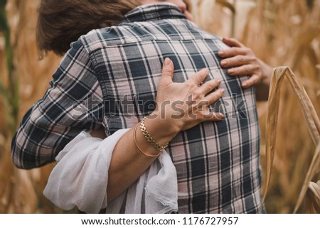 A mother hugs her adult son in the autumn field with dry corn leaves.. Maternal older hands closeup. The man in the plaid shirt. No faces.