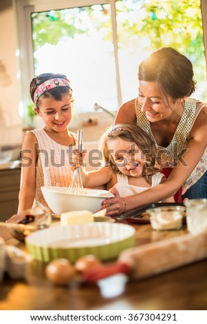 A mother is cooking with her two daughter of four and seven years old. They are smiling, wearing casual clothes. The woman is helping her youngest mixing the ingredients in a large bowl.