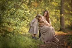 A mother is cradling a child in her arms, sitting in a sunny park. Her second daughter is looking with interest at the sleeping baby. Image with selective focus.