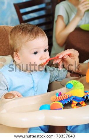 A mother is feeding her baby in the highchair at home.