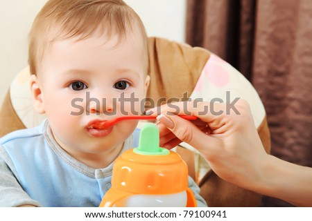 A mother is feeding her baby in the highchair at home. - stock photo
