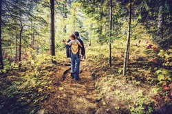 A mother is hiking on a trail in a forest with her baby in a back carrier during the autumn season.  Filtered to give retro, faded look.