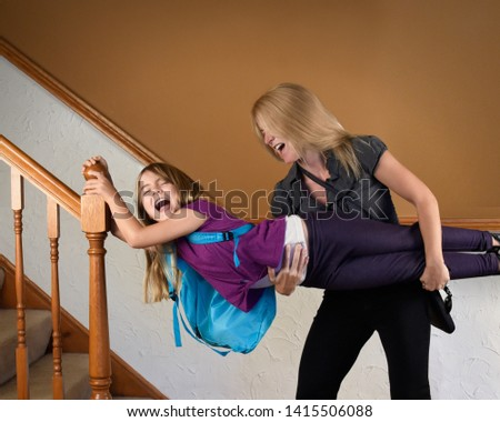 A mother is late for school and work at home rushing her child to hurry up for a funny stress concept. #1415506088