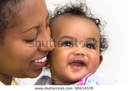 A mother kissing her smiling baby girl on the cheeks