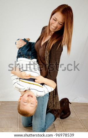 A mother laughing and playing with her young son as she holds him upside down