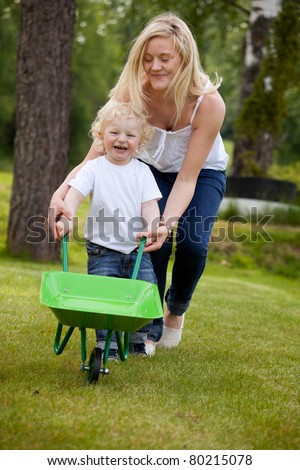 A mother playing with her son pushing a wheelbarrow outdoors