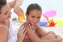 a mother putting sun cream on her daughter's shoulders