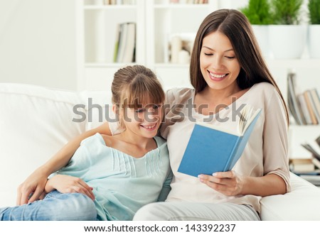A mother reading a story to her daughter.