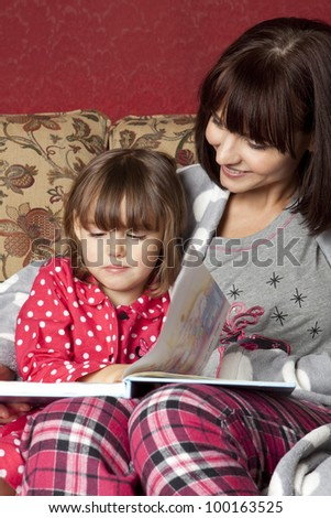 A mother reading to her daughter before bedtime
