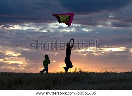 A mother runs with a kite while the son follows behind during sunset.