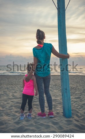A mother, seen from behind, is standing next to her daughter, resting her hand on her daughter\'s back. They are standing near a flagpole, looking out at the sea at sundown.