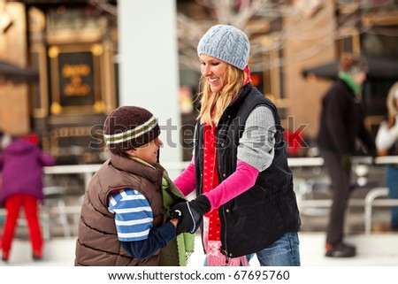 A mother teaches her son to ice skate.  Room for copy.